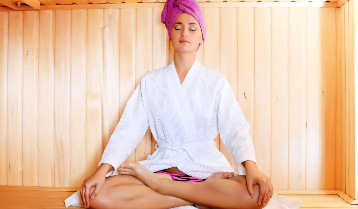 Woman sitting in a sauna meditating