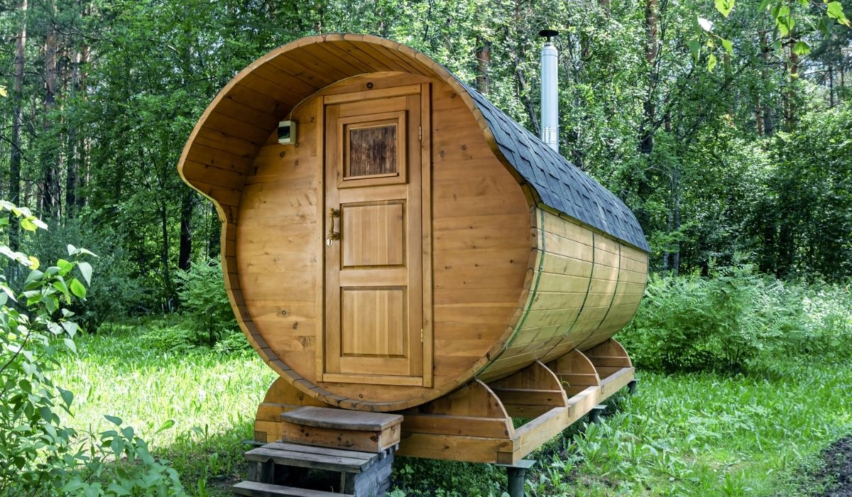 Round wooden barrel bath stands in the forest on a summer day